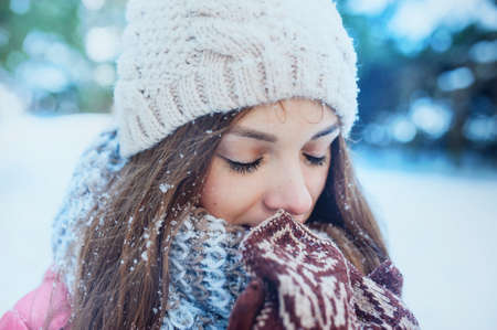 warms: The girl warms hands in mittens in winter forest. Snow on eyelashes