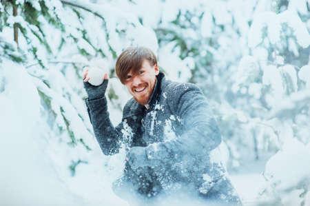 palle di neve: Stylish man with a beard playing snowballs