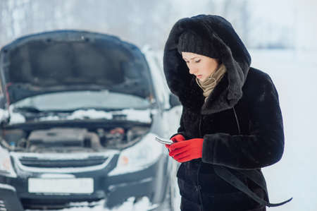 engine bonnet: Beautiful girl in a fur coat is calling on the phone near the broken car