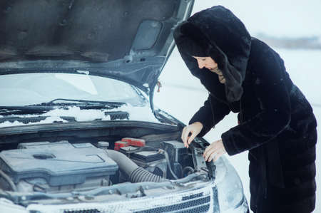 girl looks under cowl of broken car on rural road