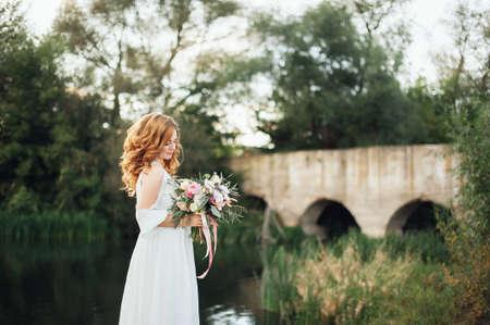 夕暮れ時の美しい大きな湖背景にブーケと花嫁。素朴な結婚式