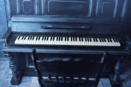 acoustically: Black antique piano and a chair. General form