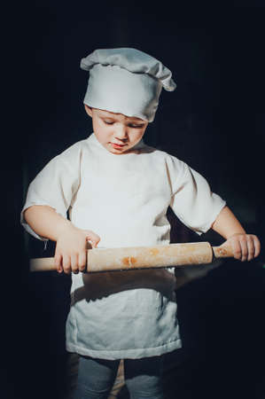 empleada domestica: Child with kitchen spoon, dressed as a cook
