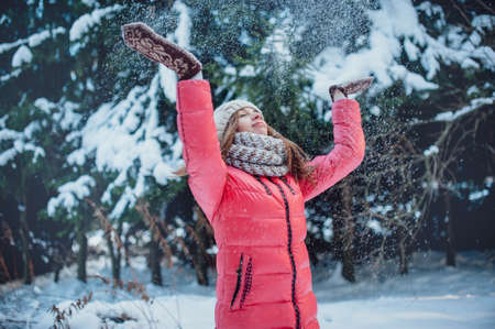 Girl in mittens throws snow in the winter forest