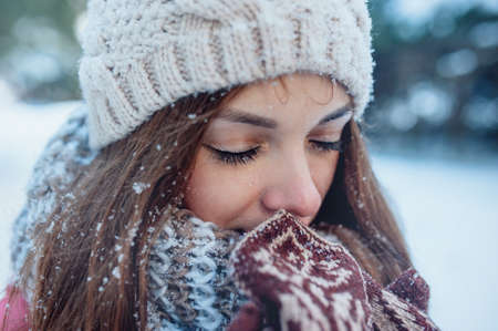 The girl warms hands in mittens in winter forest. Snow on eyelashes