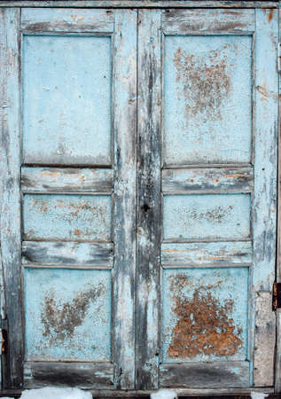 Vintage old blue wooden door with cracked paint