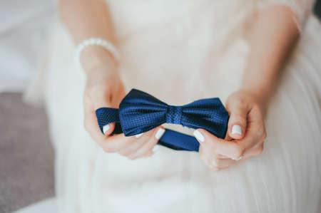 Cravatta farfalla nelle mani della sposa Archivio Fotografico - 80321084