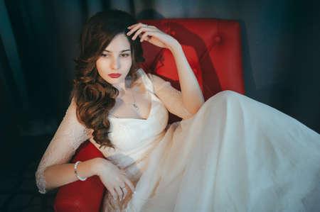 Beautiful bride posing on a red armchair Фото со стока