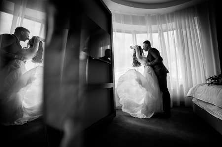 blazed: The bride and groom on the window background. Black and white photo