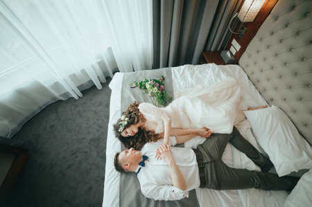 Stylish bride and groom are lying on the bed