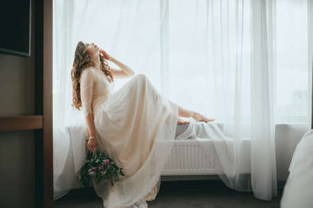Wedding preparation. Beautiful young bride in white wedding dress indoors