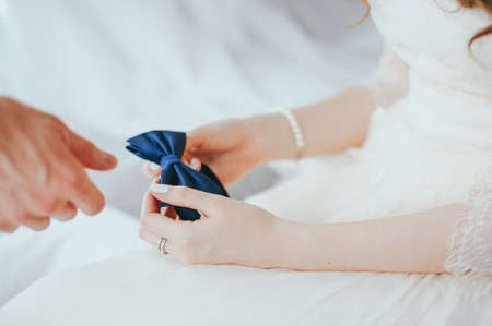 Butterfly tie in the hands of the bride