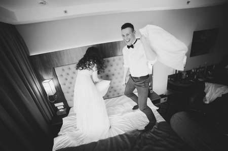 The bride and groom jumping on the bed