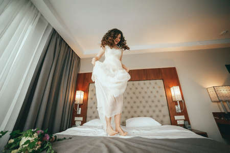 The bride jumps on the bed. fun