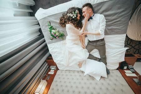 세련된 신부와 신랑은 침대에 누워있다.