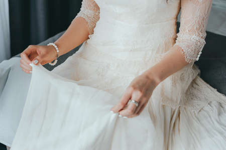 Closeup toned photo of beautiful bride tying up her wedding dress Фото со стока