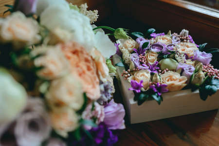 Two gold wedding rings on a cushion of flowers