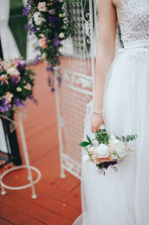 Stylish beautiful bride holds a wedding bouquet in hands