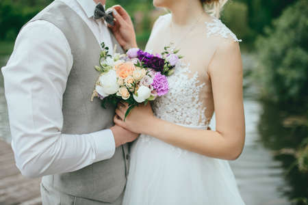 creating: Elegant gentle stylish groom and bride near river or lake. Wedding couple in love