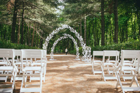 Beautiful wedding ceremony outdoors. Arch made of natural flowers. Decor