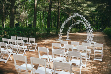 Beautiful wedding ceremony outdoors. Arch made of natural flowers.