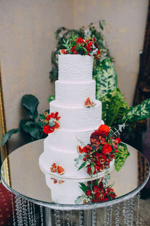 Wedding cake with red fresh flowers and fresh fruits Stok Fotoğraf - 95409677