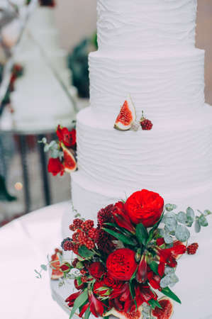 Wedding cake with red fresh flowers and fresh fruits