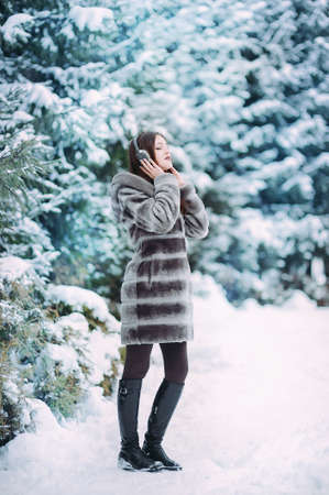 Beautiful girl meditates in winter forest. Listening to music with headphones