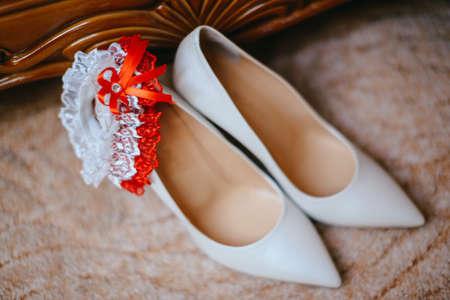 Elegante witte bruidschoenen en bruidsboeket. Bruiloft accessoires. De bruiden kousenband