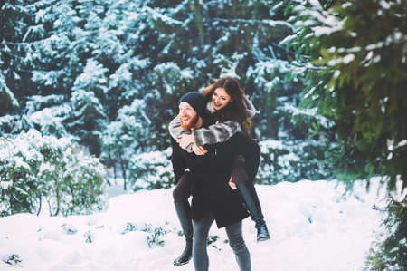 Cute young hipster couple having fun in winter park