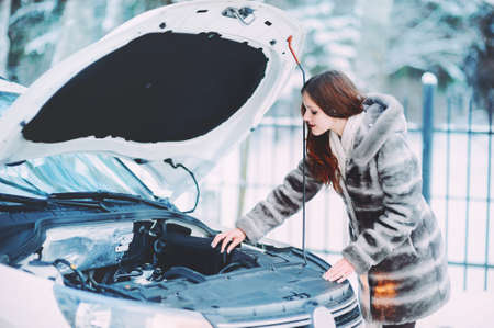 Young redhead girl looks under cowl of broken car on rural road