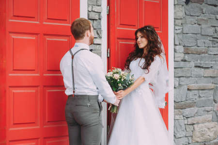 Stylish bride and groom posing on the background of the red door. Weddings in rustic style Stock Photo - 96131106