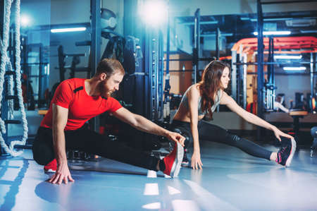 A guy and a girl in a gym doing fitness , sport . the guy winds elastic bandages on the fingers . girl drinks water and splashes it on his chest . tattoo Stockfoto