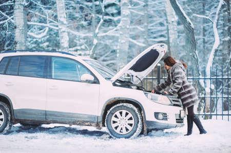 若い赤毛の女の子は、田舎の道路上の壊れた車のカウルの下に見えます