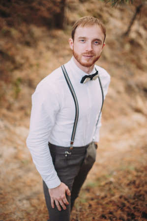 Hipster. Stylish groom with beard posing outdoors Stock Photo