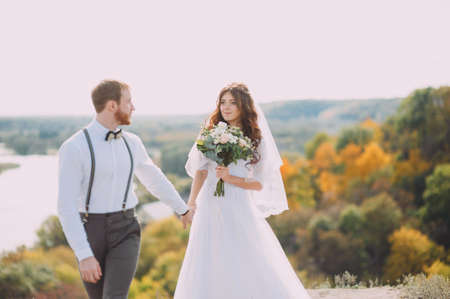 Bride and groom walking in nature. A stylish wedding. Love story. Rustic style. Stock Photo
