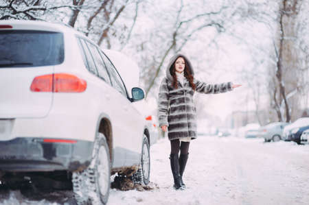 Photo slender young girl trying to stop the car on the winter road