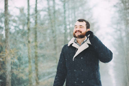 the guy with the beard is listening to music in the snowy forest Stock Photo
