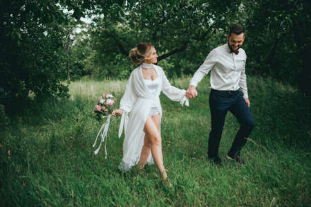 stylish bride and groom in the garden. a groom with a beard. fan art. rustic style Фото со стока