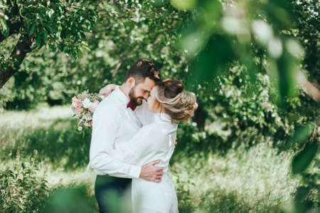 stylish groom with a beard and groom in the garden. fine art style. rustic