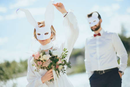 bearded groom and beautiful bride posing in rabbit masks
