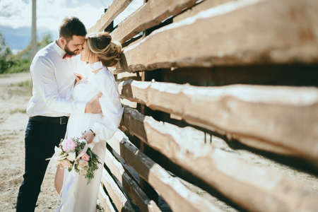 The bride in the groom poses in front of the wooden fence
