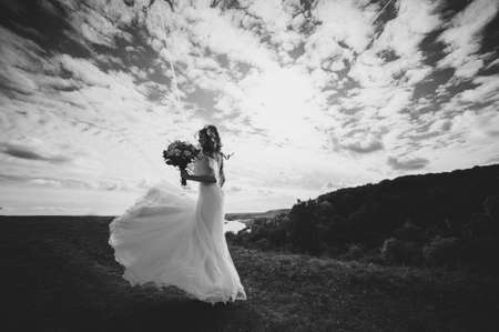 beautiful bride in a dress on the sky background. black-white
