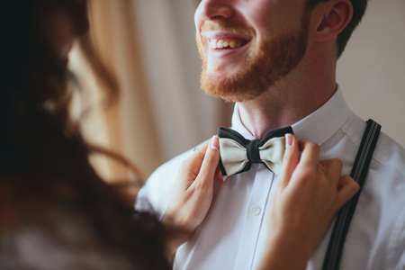 Attractive young bride adjusting the bow tie of her man.