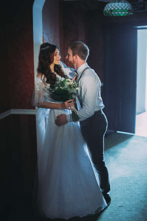 Happy bride and bearded groom on the wedding walk in the modern hotel hall on wedding Banco de Imagens