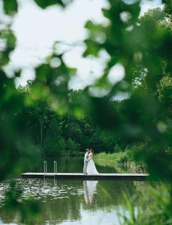 Beautiful wedding couple, bride,groom kissing and posing on the bridge near lake Stock Photo