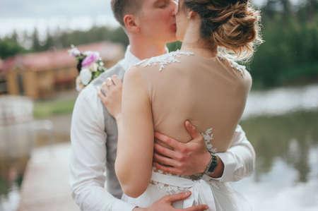 stylish bride and groom at the lake at the wedding