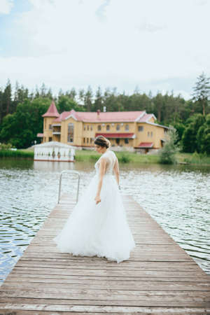 Portrait of a young beautiful bride on a background of a gorgeous view of the river and fields. Wedding day.