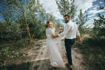 Beautiful wedding photosession. Handsome groom in blue formal suit and his elegant bride in dress and veil with bouquet with beautiful hairdress embrace on a walk in the big green park on sunny day.