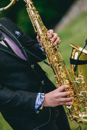 a saxophonist plays the saxophone. hands close up